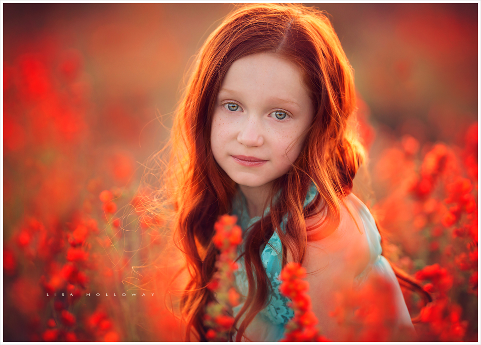 Little girl with red hair and a blue dress stands in a field of orange flowers las vegas child photographer 03