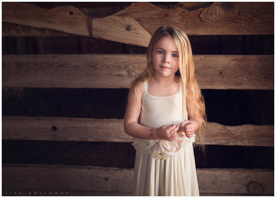Little girl with blue eyes and long blonde hair poses for her child portrait session in
