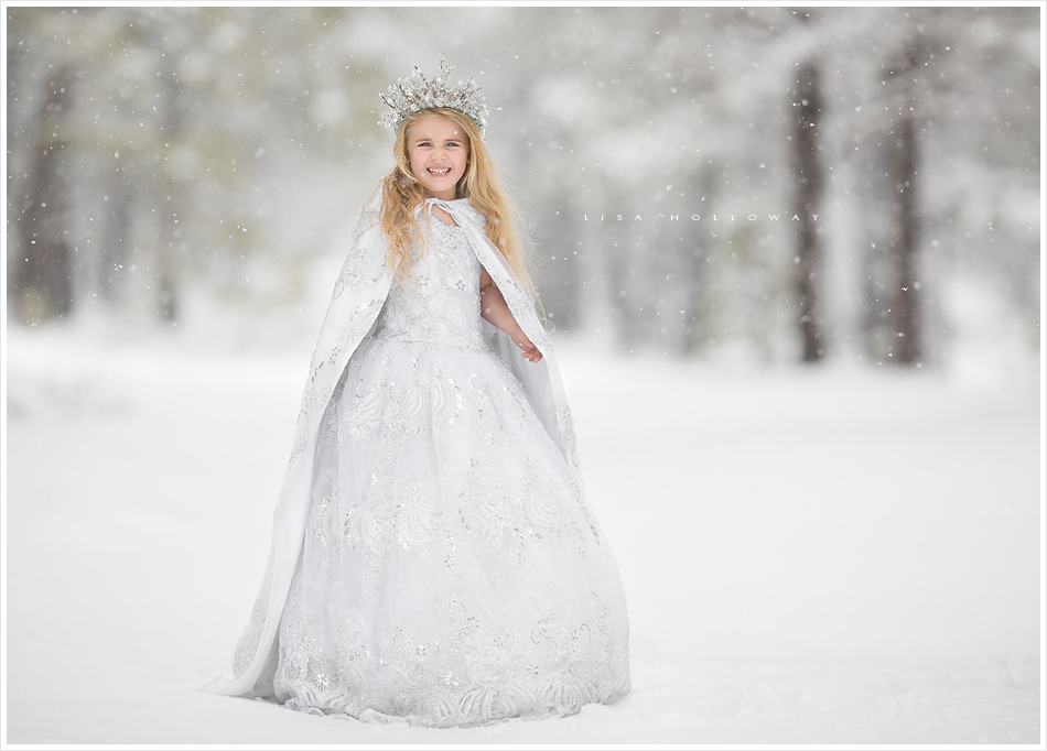Pretty little girl with blonde hair has her portraits taken as a snow princess in the