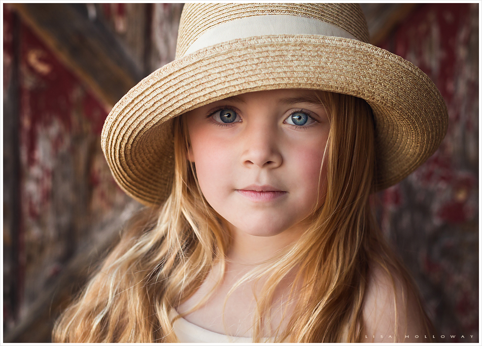 Closeup portrait of a pretty little girl with long blonde hair and blue eyes wearing a