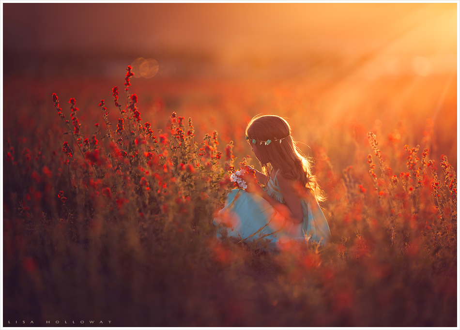 Beautiful little girl picks ourange flowers outdoors for her child portrait session near las vegas