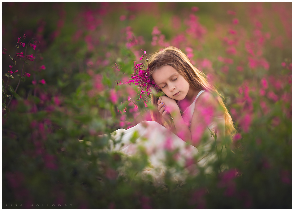 Cute little girl picks pink flowers outside in a field for her child portrait shoot near