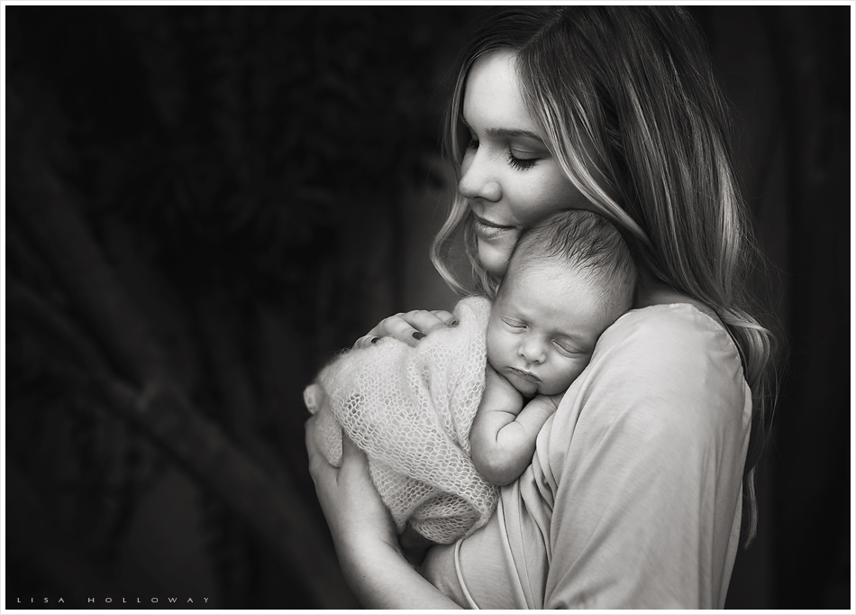 Justine ackley holds her newborn baby boy during their newborn portrait session in their home near
