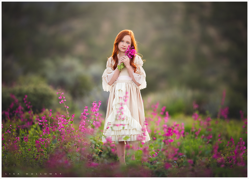 Beautiful redheaded little girl picks pink flowers outdoors for her child portrait session near las vegas