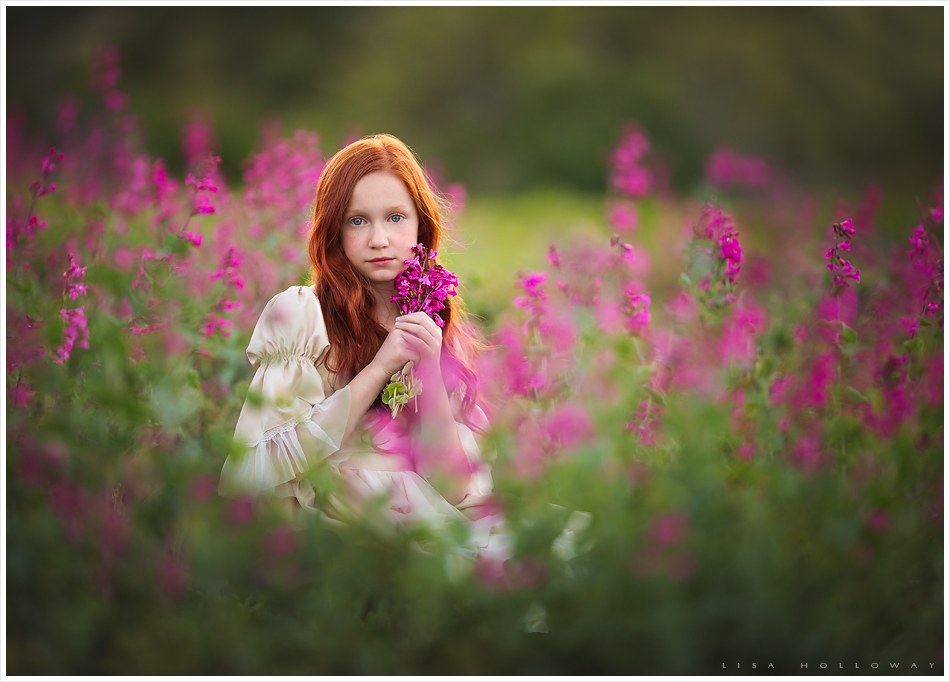 Beautiful little girl with red hair picks pink flowers outdoors for her child portrait session near