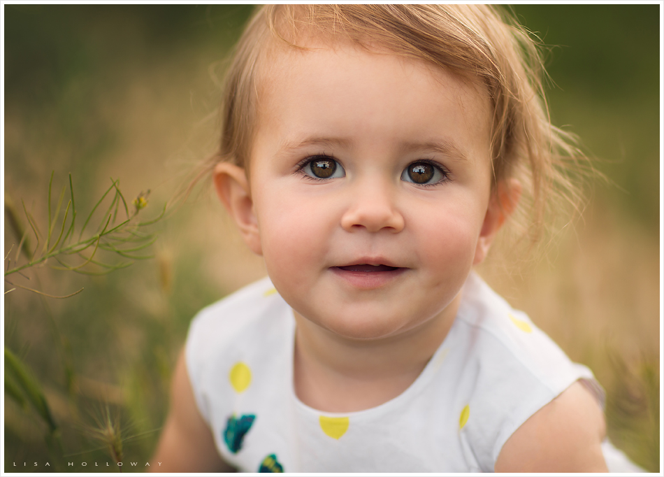 Closeup portrait of a cute little toddler girl during her familys outdoor portrait session near las