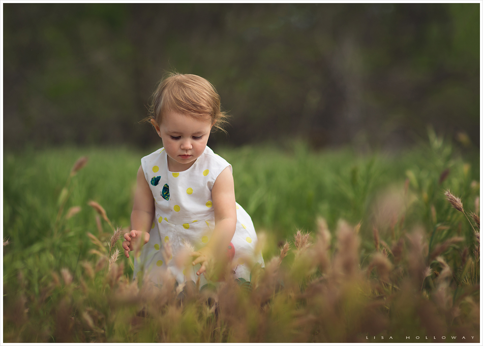 Cute toddler girl plays outside during her family and child portrait session near las vegas
