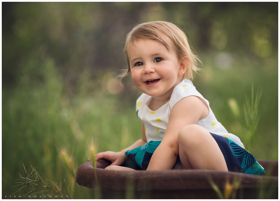 Cute toddler girl plays outside in a vintage wagon during her family and child portrait session