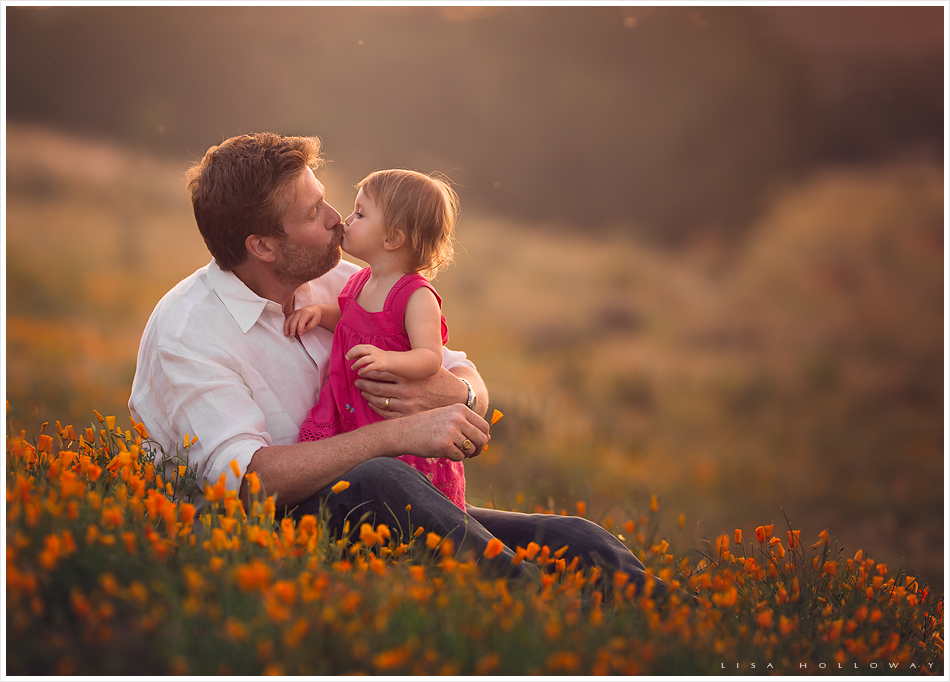 Cute toddler girl wearing a pink dress gives her dad a kiss in a field of
