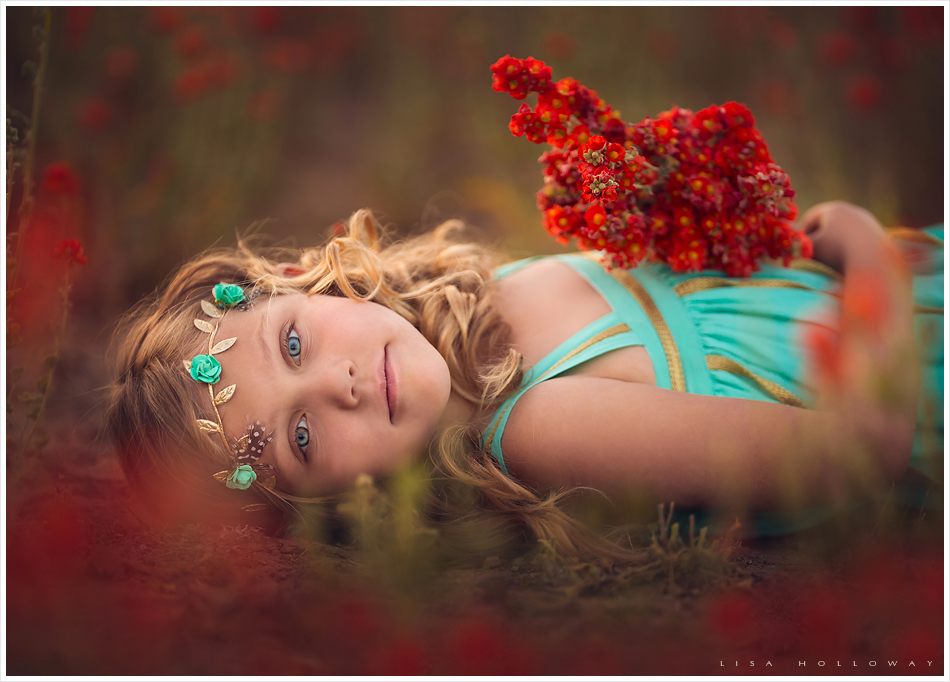 Little girl picks red wildflowers in a beautiful field near Las Vegas