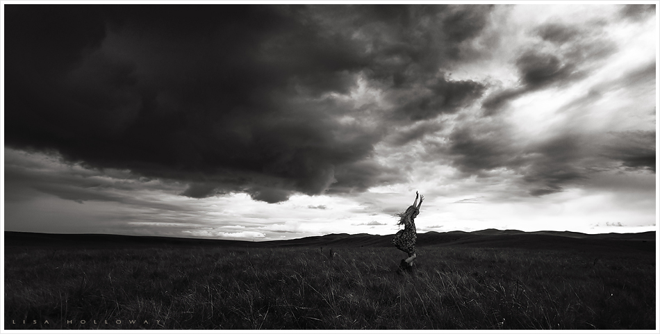 Little girl runs and dances across a field under dark storm clouds