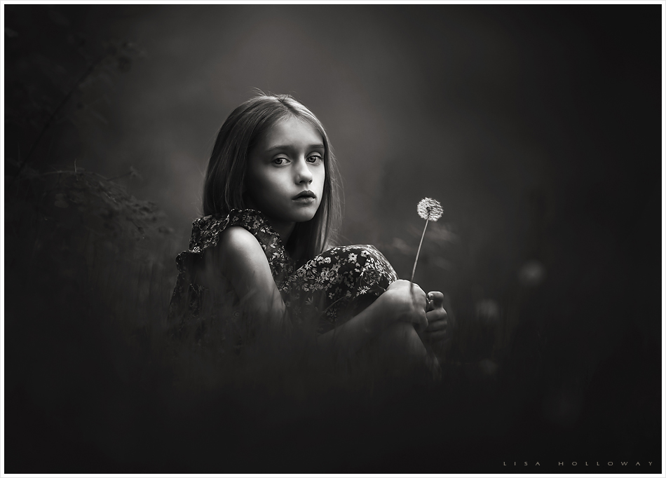 Black and white portrait of a cute little girl holding a dandelion