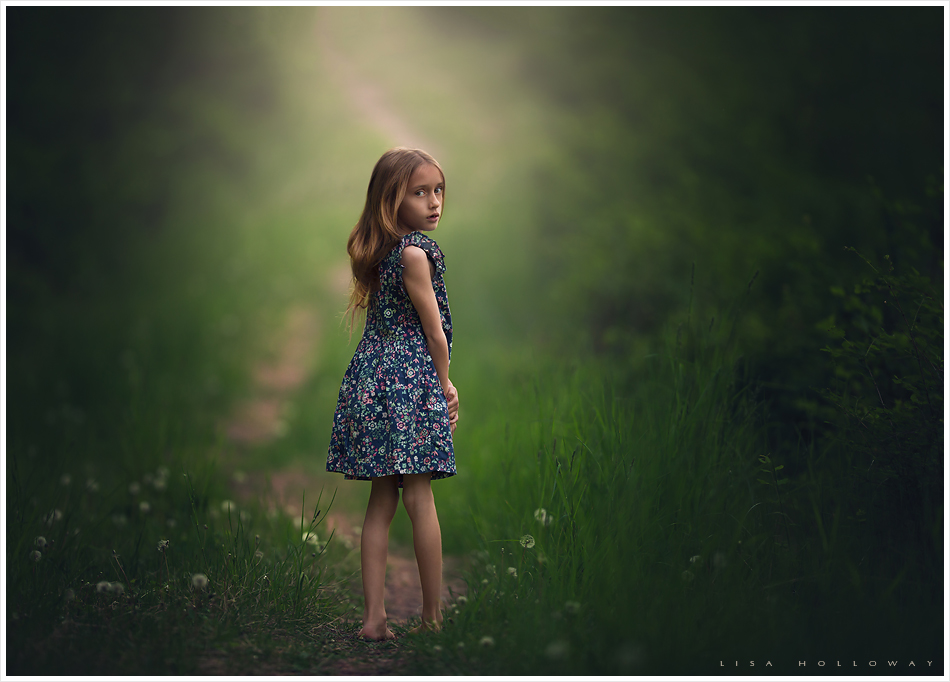 Outdoor portrait of a little girl following a path through the green forest