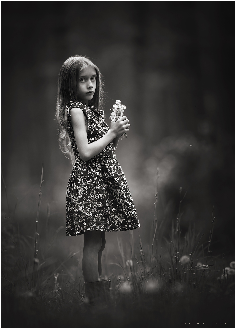 moody black and white portrait of a little girl with long hair standing outside