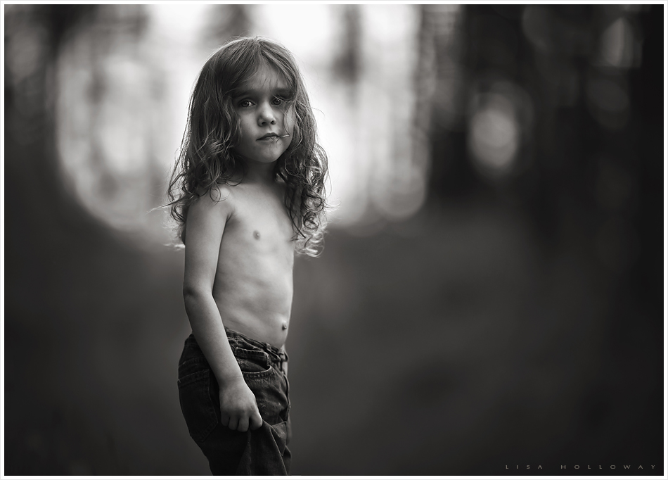 Moody black and white portrait of a little boy with long, curly hair taken outdoors, reminiscent of a Sally Mann photo. Image taken by LJHolloway Photography of Las Vegas, NV.