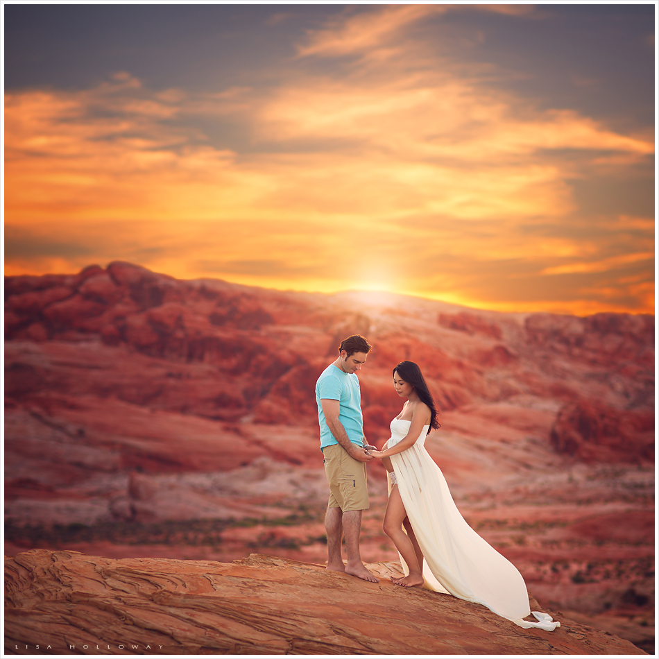 Beautiful pregnant woman poses with her husband for her maternity photo session on the red desert rocks outdoors near Las Vegas at sunset