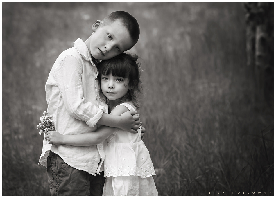 Moody black and white portrait of a brother and sister hugging outdoors on mt charleston