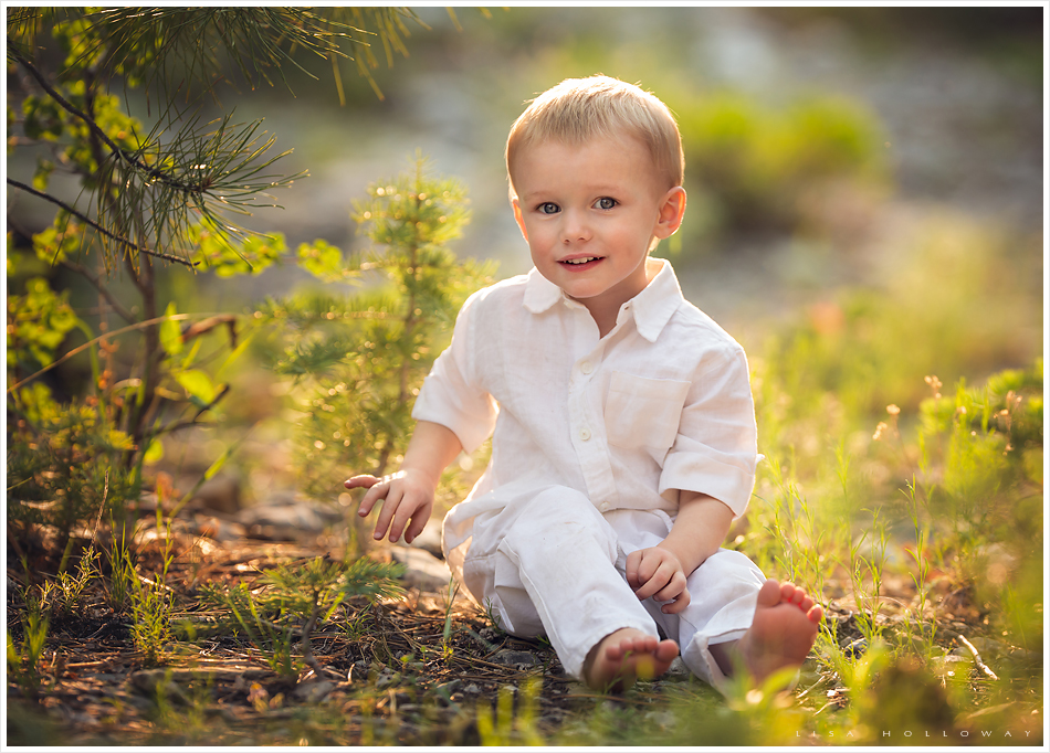 Vegas child photographer gallery cute baby boy wearing white sits outside in the forest for a portrait taken on mt