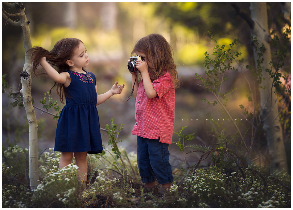 2 cute children take photos of each other in the forest on mt. charleston near las vegas during a photo session