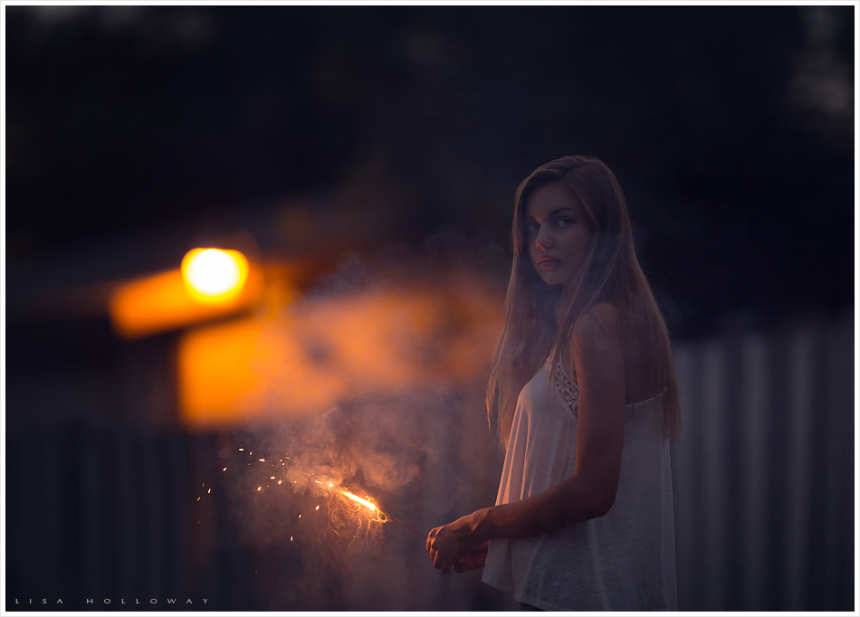 teen girl holds a sparkler on the 4th of july in kingman az