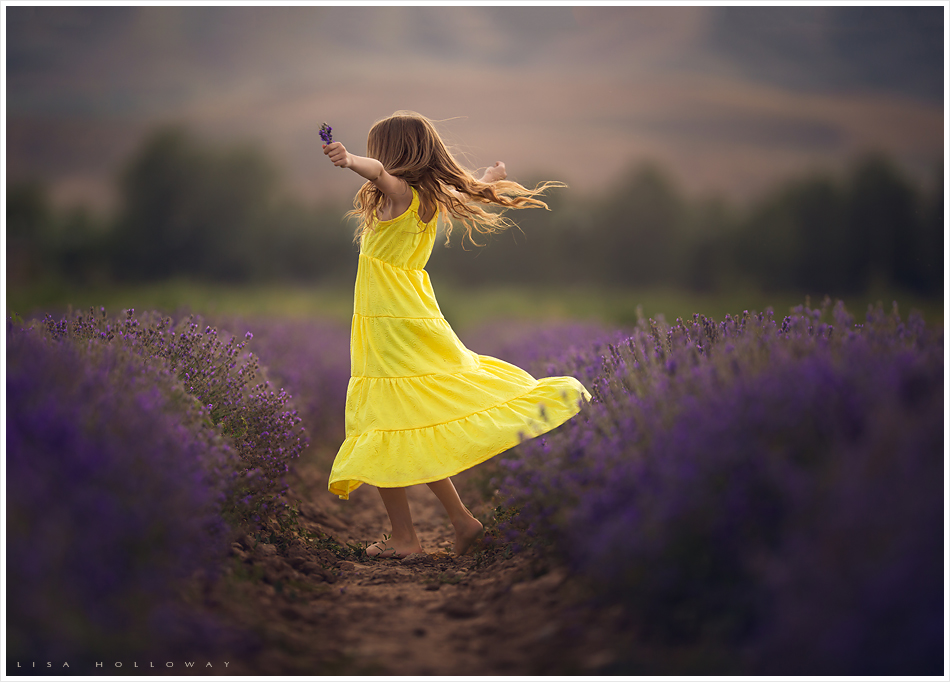 cute little girl in a yellow dress dances and twirls in a lavender field