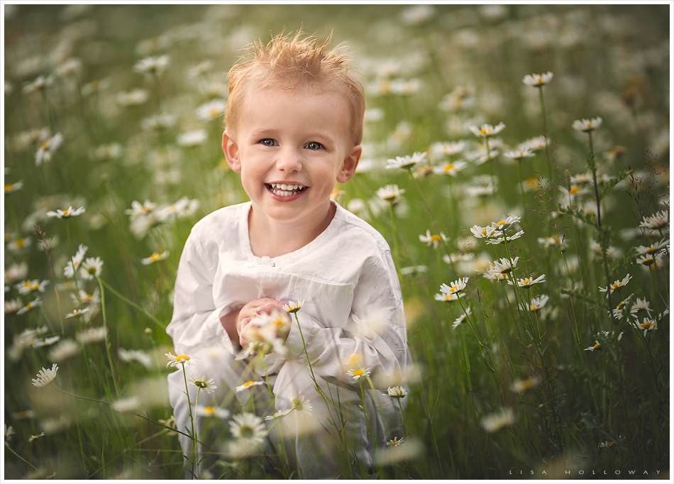 adorable toddler boy with blonde hair smiles while sitting in a field of daisies for a portrait taken outdoors in a field near las vegas nv