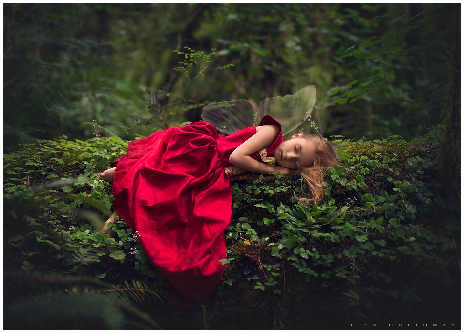 little fairy dressed in a red gown takes a nap on a moss covered log in the rain forest in washington state