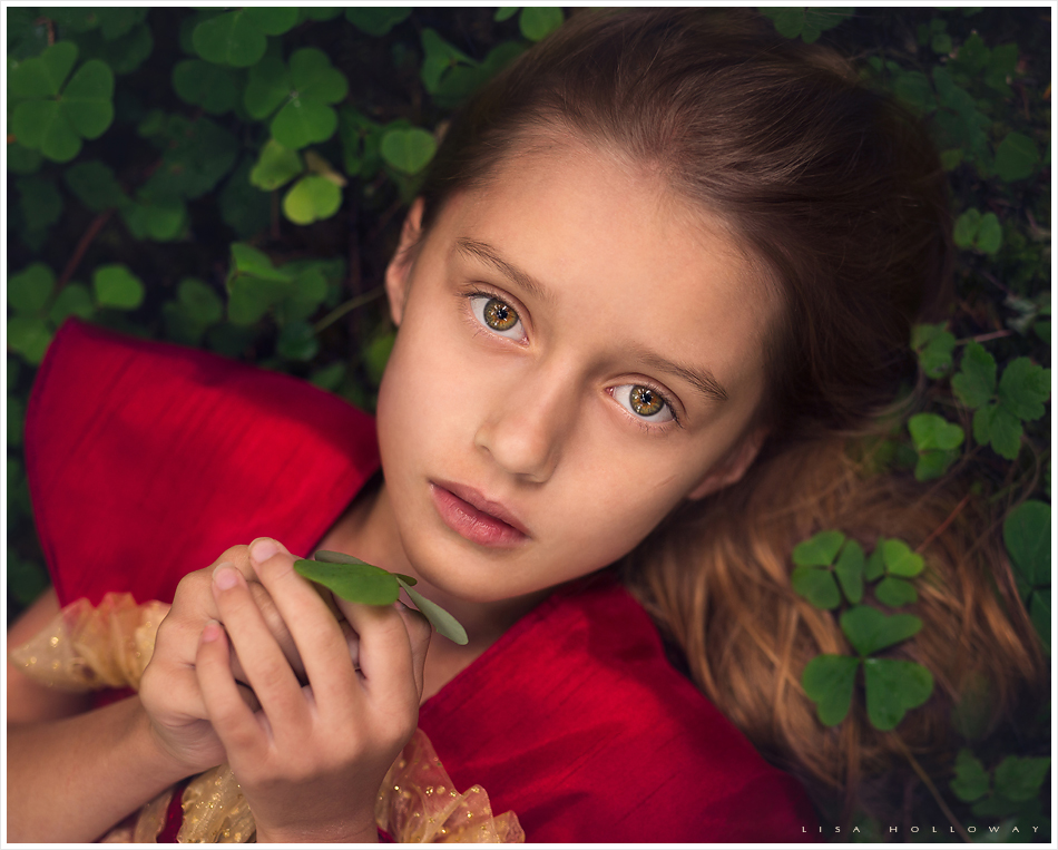closeup portrait of a pretty little girl with green eyes laying in a clover patch wearing a red dress outdoors in the Ho'h rainforest in washington state