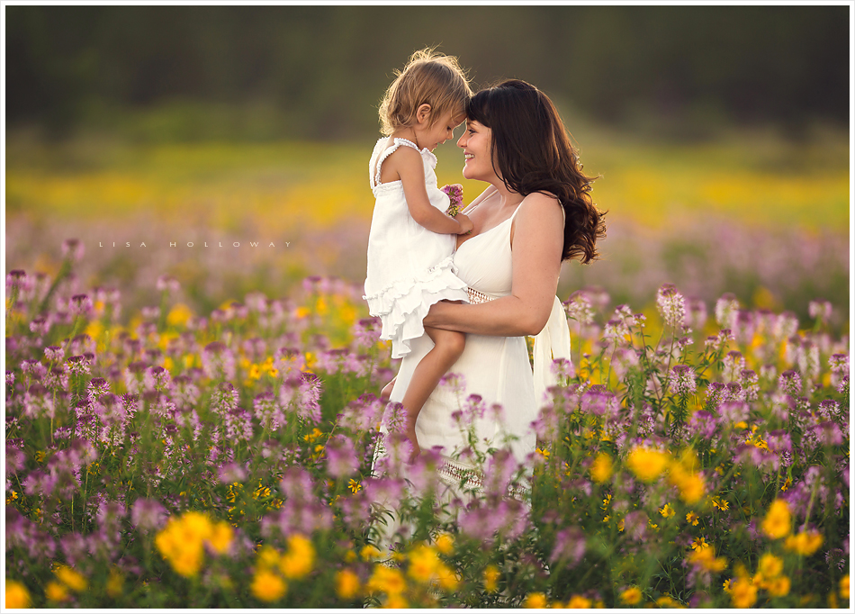 mother and daughter hug in a field of wildflowers during their outdoor portrait session near las vegas nevada