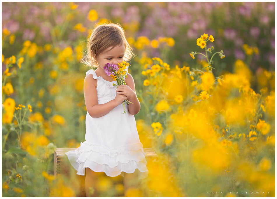 cute little girl smells flowers in a field of wildflowers during her outdoor portrait session near las vegas