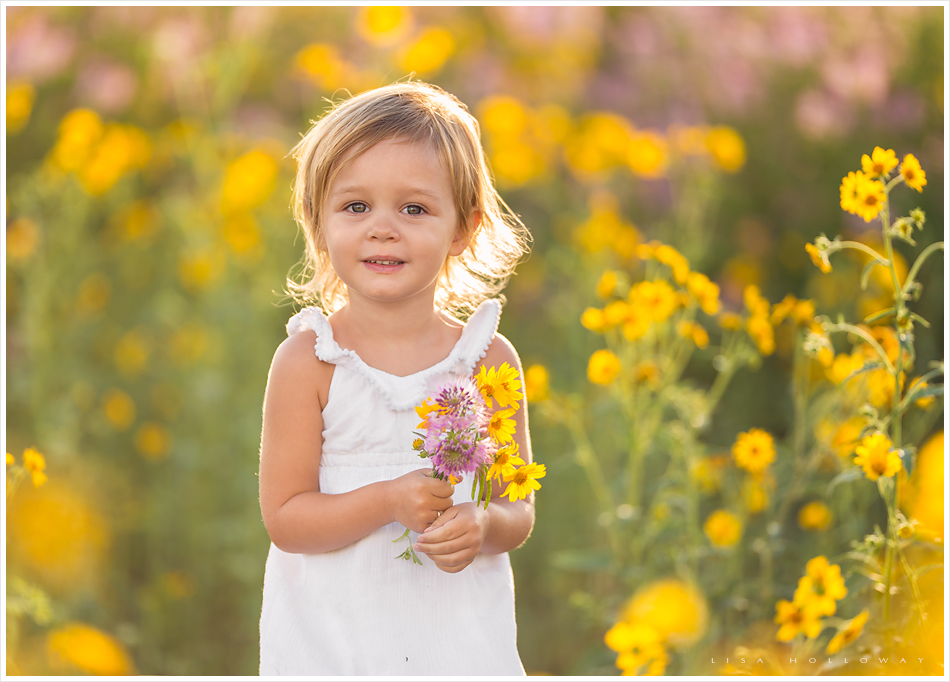 Cute little girl picks yellow and purple flowers outside in a field during her child portrait