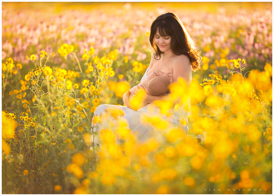 mother nurses her baby boy in a field of wildflowers outside in a field during a portrait session near las vegas nevada