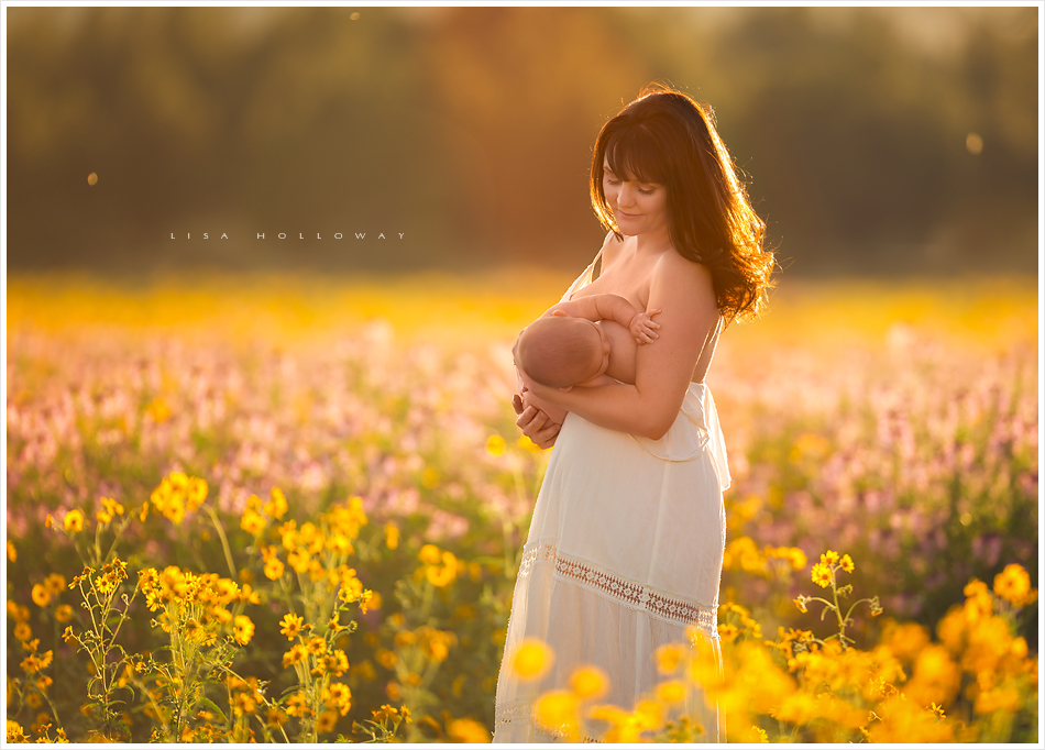 mother breastfeeds her baby boy in a field of wildflowers outside in a field during a portrait session near las vegas nevada