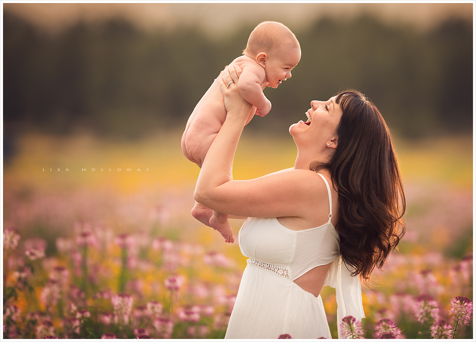 a mother plays with her baby boy in a field of wildflowers during their outdoor portrait session near las vegas nevada