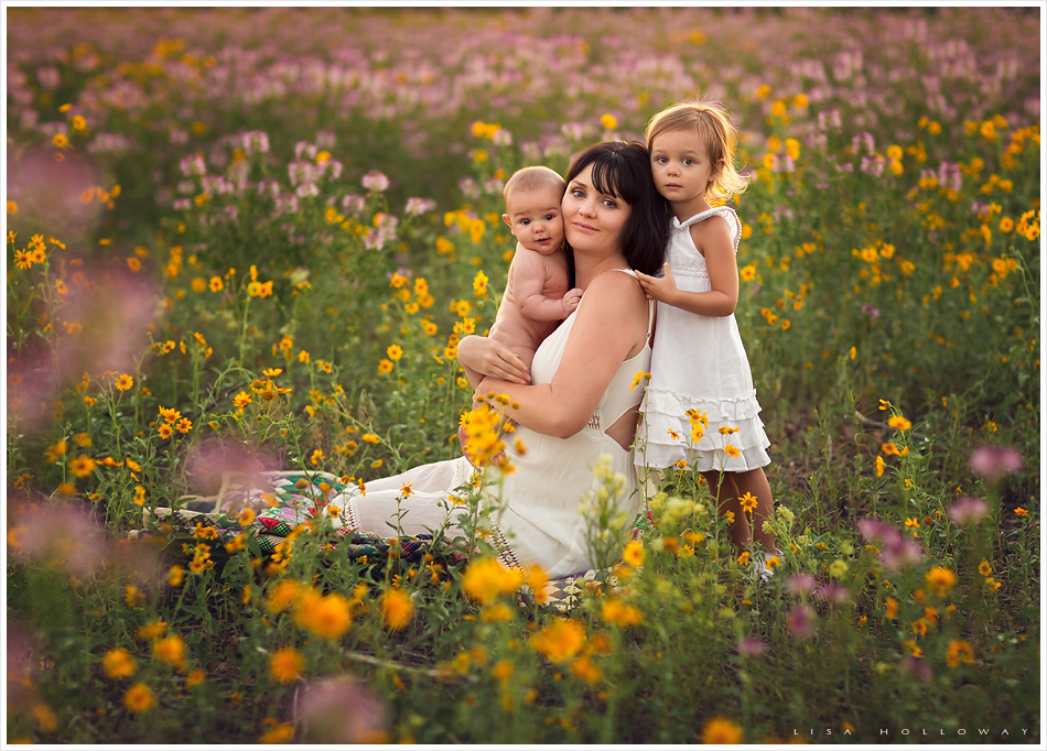 Family picture of a mother and her 2 children outdoors in a field of wildflowers near
