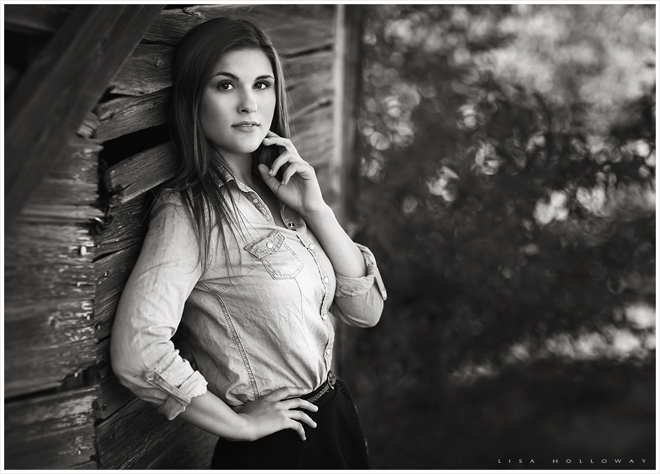 beautiful senior girl poses next to a barn wall outdoors near las vegas, nv for her senior portrait session