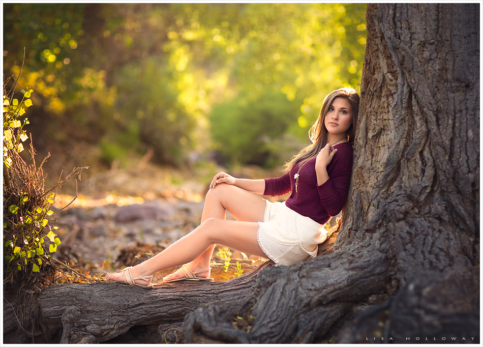 beautiful senior girl sits next to an old tree outdoors near las vegas, nv for her senior pictures