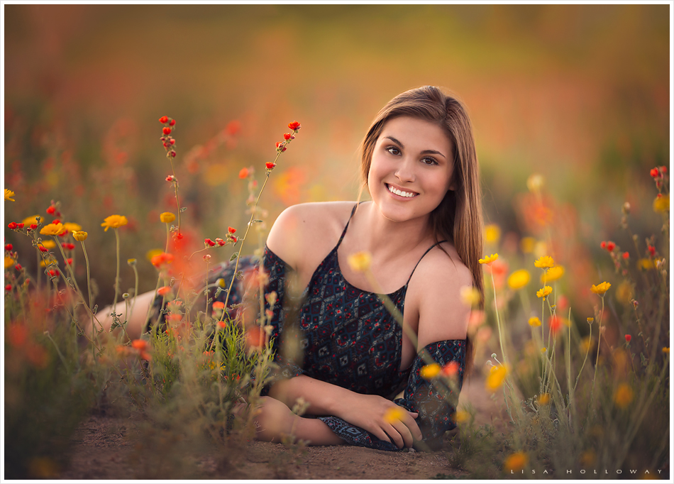 beautiful senior girl poses outside in a field of wildflowers for her senior pictures near las vegas, nv