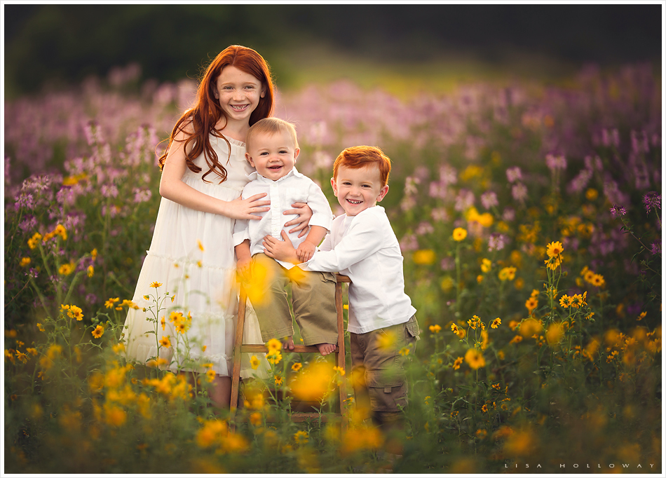 3 cute redheaded siblings pose for professional pictures in the wildflowers in williams arizona