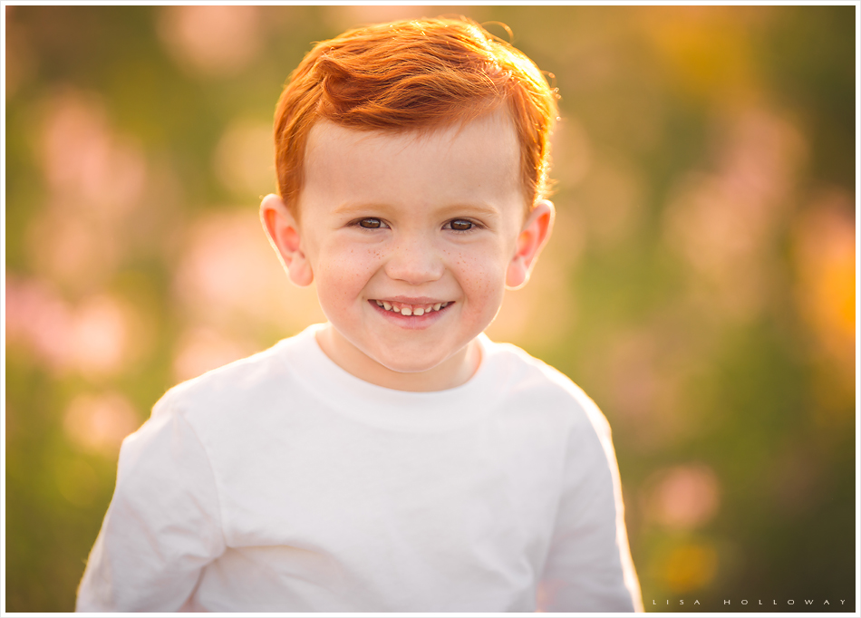 closeup portrait of a cute redhead boy with freckles outdoors in the wildflowers