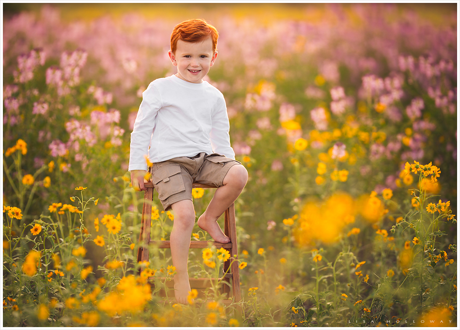 portrait of a cute redhead boy with freckles outdoors in the wildflowers
