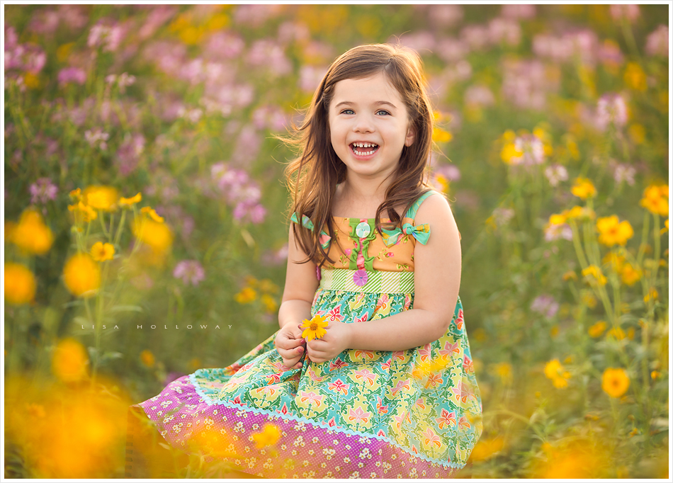 adorable little girl laughs during an outdoor portrait session in the wildflowers near las vegas