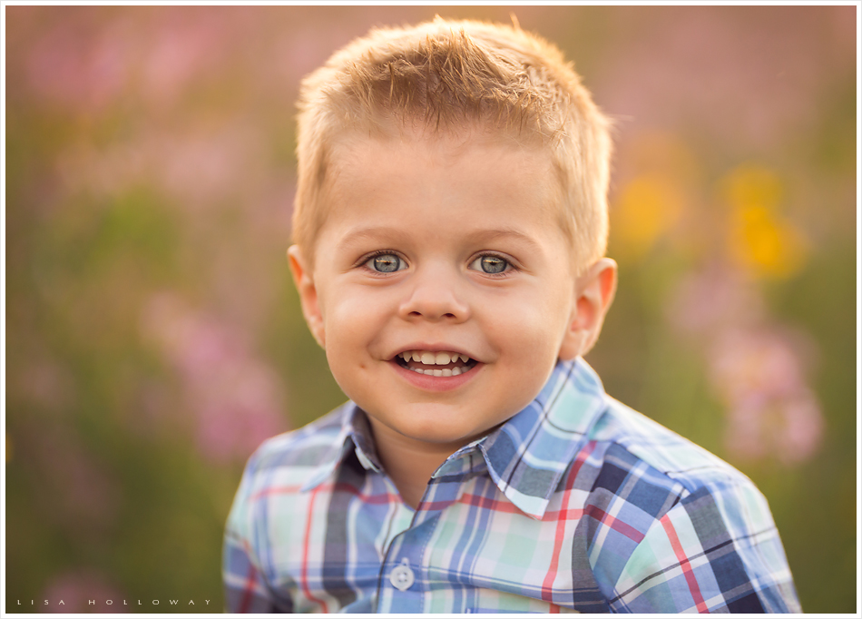 closeup portrait of a cute little boy with blonde hair and blue eyes outside in a field of wildflowers near williams arizona