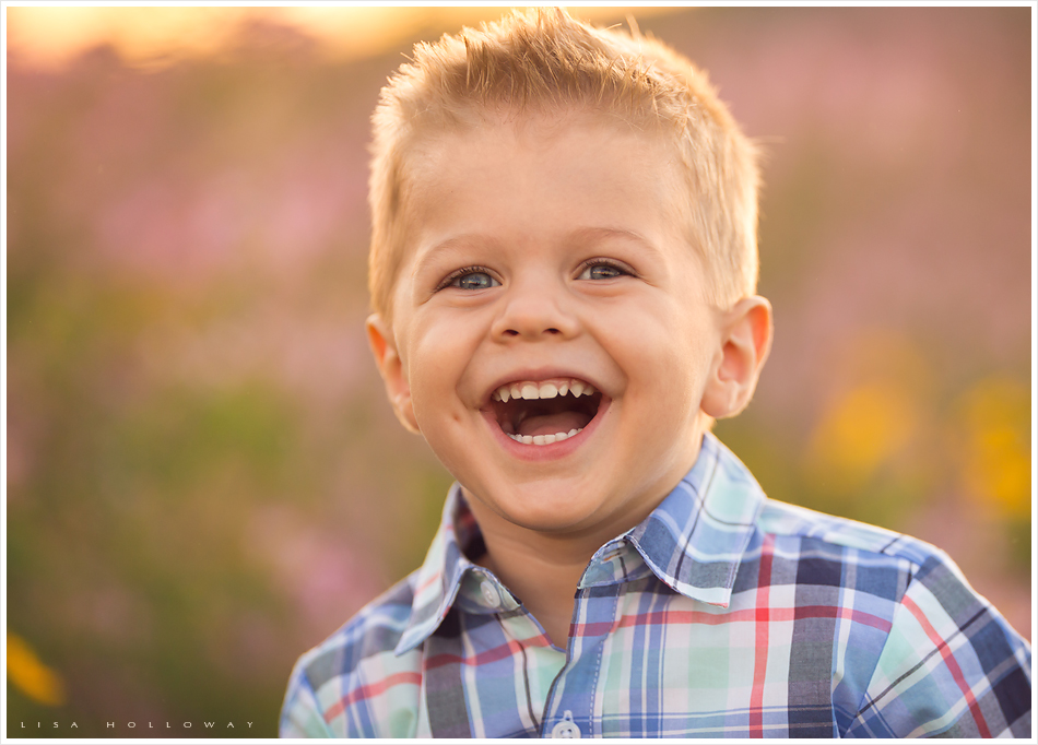 closeup portrait of a cute little boy with blonde hair and blue eyes laughing outside in a field of wildflowers near williams arizona