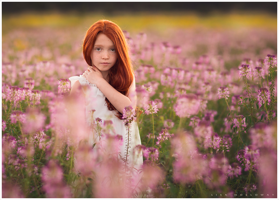 pretty redheaded girls poses outdoors in a field of wildflowers