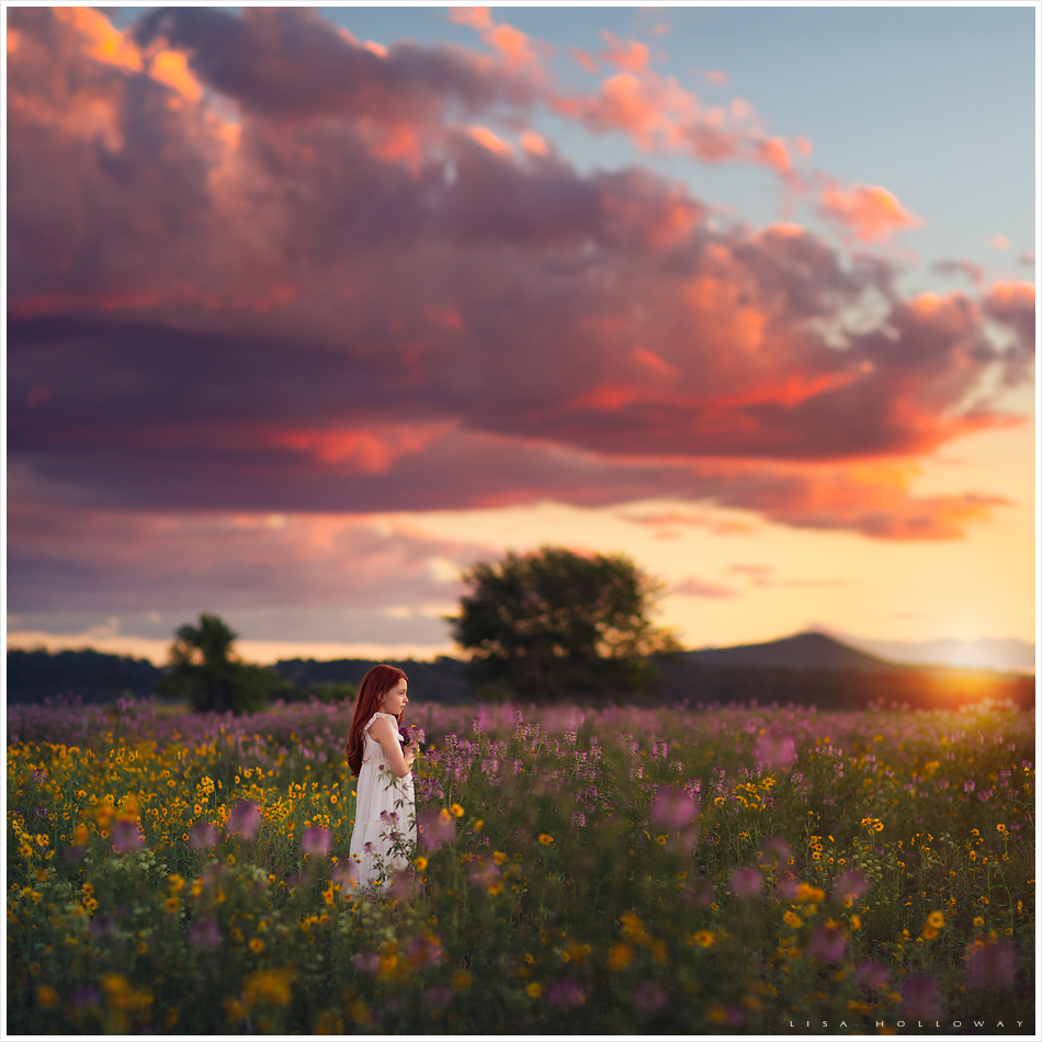 pretty redheaded girls poses outdoors in a field of wildflowers at sunset