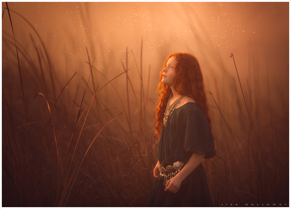 Beautiful redheaded girl with freckles has her portrait taken outdoors at sunset in a foggy area with tall golden grass near Las Vegas.