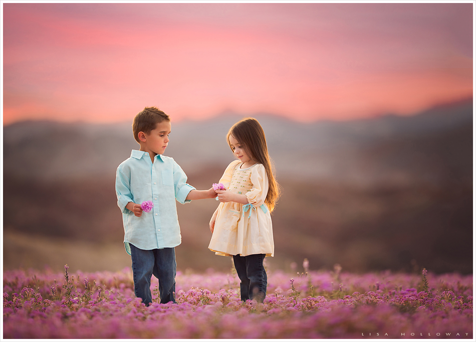 Cute little boy hands a little girl a flower while they have their picture taken in