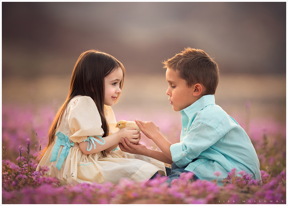Very cute little boy and girl hold a baby c hick together in a field of pink wildflowers for a portrait outside near Las Vegas. LJHolloway Photography is a Las Vegas Child Photographer.