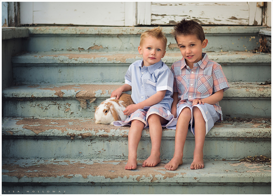 2 cute little boys wearing the chambray and peach Well Dressed Wolf outfits pose on stairs with mint green peeling paint with their pet bunny. LJHolloway Photography is a Las Vegas Child Photographer.